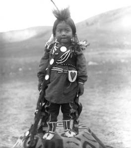 Title Nez Perce boy, Colville Indian Reservation, Washington, ca. 1903. Photographer Latham, Edward H. Studio Location United States--Washington (State)--Nespelem Date ca. 1903 Notes Young boy stands outside on blanket. He wears feathers and decorations in his hair, long shirt over leggings, beaded moccasins, necklaces, bracelet, vest, and leather pouch attached to belt. A sash with ornaments is draped across his chest. Caption on negative sleeve: Little Indian boy dolled up. Note from unidentified source: Young Nez Perce boy. Subjects Portraits--Washington (State) Nez Perce Indians--Clothing & dress Nez Perce Indians--Children Blankets Bags Location Depicted United States--Washington (State)--Colville Indian Reservation Object Type Photographs Negative Number NA1010 Collection Edward H. Latham Collection no. 409 Repository University of Washington Libraries. Special Collections Division