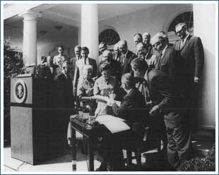 President Lyndon Johnson signs the Wilderness Act of 1964 in the White House Rose Garden. Also pictured are Interior Secretary Stewart Udall, Senator Frank Church, Mardy Murie, Alice Zahniser, and Representative Wayne Aspinall, among others.