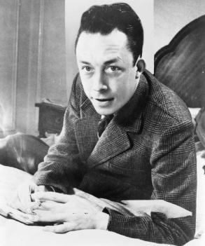 Albert_Camus,_gagnant_de_prix_Nobel,_portrait_en_buste,_posé_au_bureau,_faisant_face_à_gauche,_cigarette_de_tabagisme